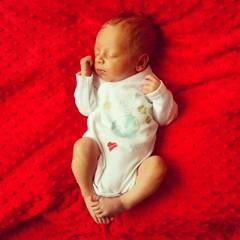 Beautiful baby newborn love earth red background