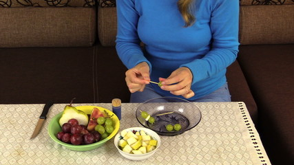 hand string grape pear fruit on  stick and put pan on table
