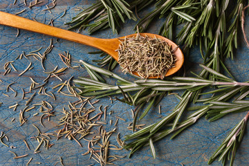 Rosemary and a spoon on a blue table