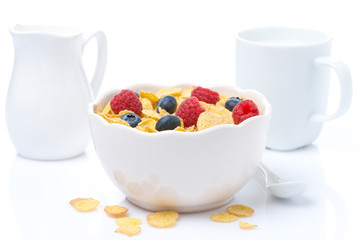 cornflakes with fresh berries in a bowl and milk, isolated