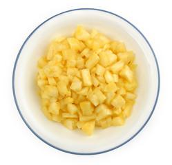 Chopped pineapple chunks in a white bowl