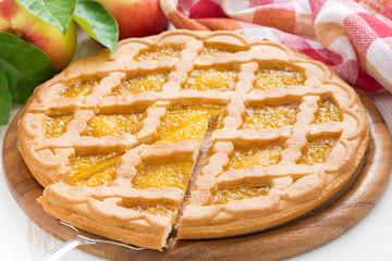 Sliced apple pie on white wooden table