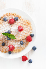 thin Belgian waffles with berries, top view, vertical