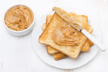 toast with peanut butter on a plate, top view
