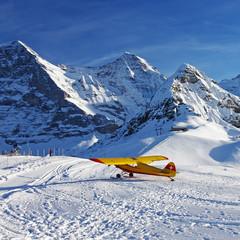 Yellow airplane at the Swiss winter mountain ski resort