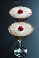 two-layer chocolate dessert decorated with cherries