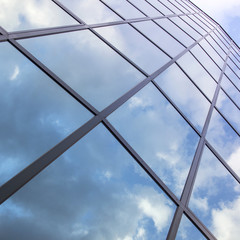 reflexions of clouds and blue sky in facade of modern building