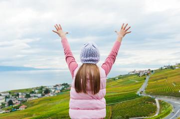 Kid girl stand between Lavaux vineyards