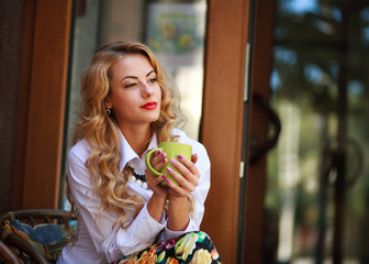 Pensive woman sitting with coffee cup and has a rest