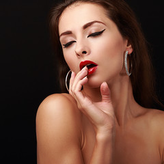 Sexual young woman with finger near red lips. Closeup