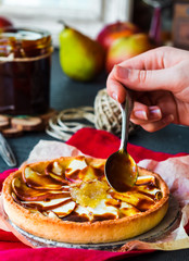 apple tart with pear jam pour caramel, hands