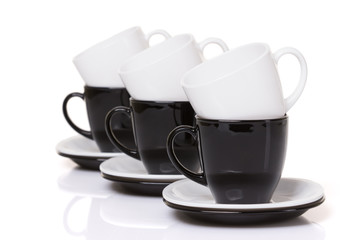 Black and white cups on the stack of the plates.