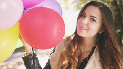 Beautiful brunette with colorful balloons in autumn park.