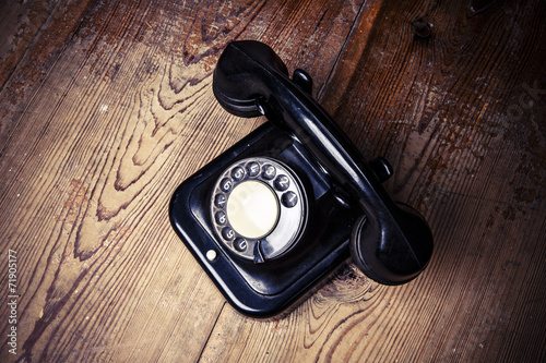 Foto op Canvas Retro Old black phone with dust and scratches on wooden floor
