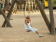 canvas print picture - little girl in a white dress on  swing at playground