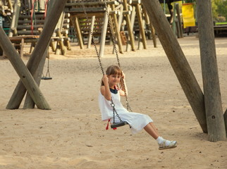 little girl in a white dress on  swing at playground