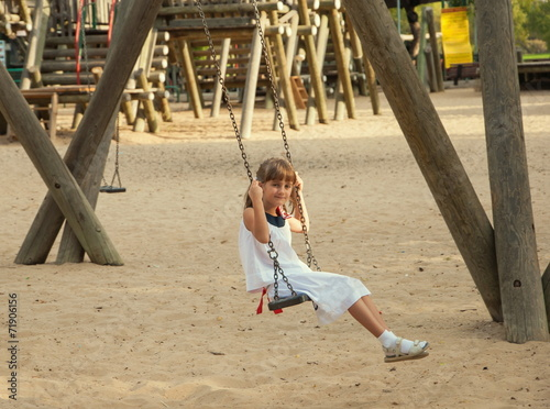 canvas print picture little girl in a white dress on  swing at playground
