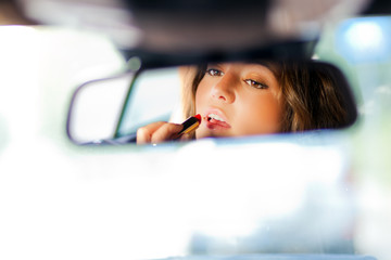 cute blond woman applying lipstick in a car