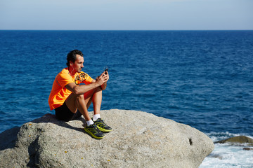 Male runner using mobile smart phone resting after workout