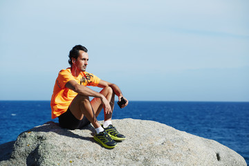 Sportsman in fluorescent t-shirt rest and relax after training