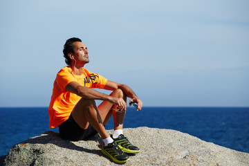 Relaxed fit man listening to music sitting on sea rocks