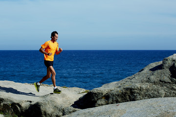 Runner in fluorescent t-shirt runs over sea rocks at morning jog