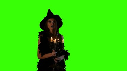 Halloween witch blows out the candles  on green screen