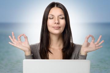 Hübsche Frau sitzt meditierend vor einem Laptop Computer