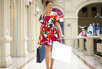 Young woman in sexy dress walking in the shop