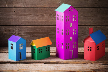 A paper houses stands over a wooden background.