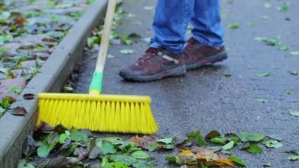 Worker sweeps leaves