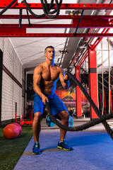 battling ropes man at gym workout exercise