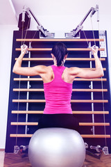 Beautiful girl doing exercise on kinesis. Working out