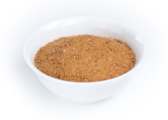 Coconut sugar in a white bowl against white