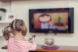 little cute girl with remote changes channel on tv poster