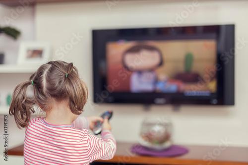 Leinwandbild Motiv little cute girl with remote changes channel on tv