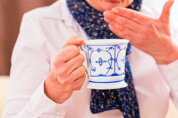Seniorin trinkt Tee und kuriert ihre Erkältung
