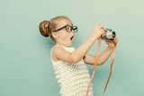 Fototapety child holding a instant camera