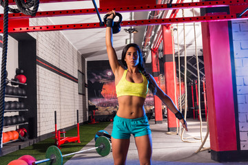 brunette girl at gym lifting a kettlebell