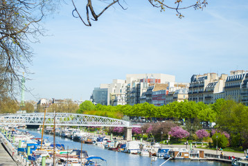 Canal of Paris with boats and trees with buildings