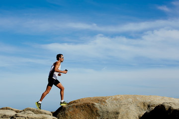 Male runner in sportswear running down over the rocks