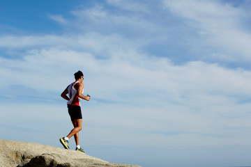 Young athlete running down over rocks at workout outdoors