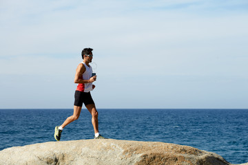 Middle age man at workout outdoors jogging along the sea