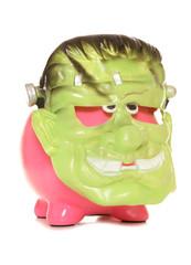 Piggy bank wearing a frankenstien halloween mask