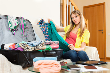 woman packing a suitcase for travel