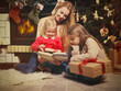 Young mother and her two little daughters with Christmas gifts r