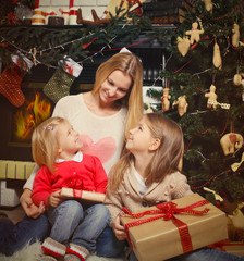Young mother and her two little daughters with Christmas gifts b