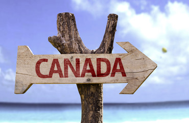 Canada wooden sign with a beach on background