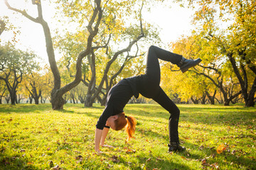 Woman doing yoga in autumn park
