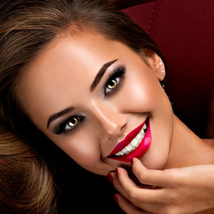 Smiling woman with dark brown eye makeup and bright red lips